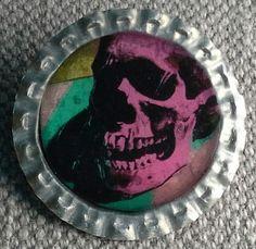 """Broche """"capsuline"""", création . Support capsule de bière argentée.  Image : Vanité. Andy Warhol La broche est recouverte de résine. Diamètre 34mm"""