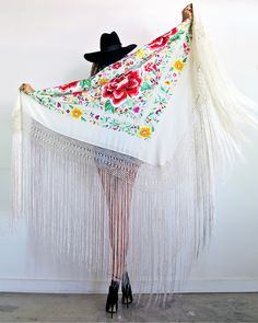 """In Gypset Heaven! Truly stunning hand embroidered Spanish shawl! Stunning bright bold floral embroidery on Ivory ground.  Beautiful extra long fishnet fringe that flows so stunningly with every movement! Incredible large size to be worn and adorned or used as a home decoration/throw, or should I say, art piece to be admired. Measurement is 52"""" x 55"""" (not including the fringe)Fringe is 24' long"""