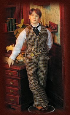 Charles wears a wool suit and a cotton shirt. A black silk scarf is held by a black diamond pin. He has a gold watch on the waistcoat.