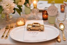 A spray painted toy car parks atop place card and napkin, setting a color tone for the rest of the table--bottled lemonade with gold bottle cap, gold utensils, and embossed place and menu cards.