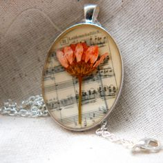 resin jewelry pressed flower necklace. peach daisy mum pressed botanical Pendant on music. $55.00, via Etsy.