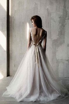 Nude shaded open back wedding gown decorated with handmade lace appliques