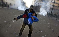 An Egyptian protester evacuates an injured boy during clashes near Tahrir Square, on January 25, 2013. (AP Photo/Khalil Hamra)