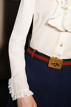 A belt from the Gucci Gift selection, in ribbed green-red-green canvas Web, trimmed with faded brown leather and featuring an antique brass plaque buckle embossed with a bee. Worn with a washed Oxford shirt and a tweed skirt.