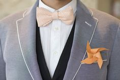 Peachy bow tie, two-toned, white-line suit, and orange windmill boutonnieres.