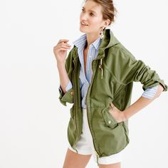 Green jacket, blue striped shirt, white pans and funky earrings with hair pulled back.