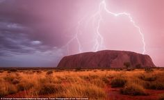 Uluru, or Ayers Rock, is illuminated by several bolts of lightning as a storm rolls throug...