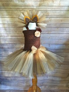 Your little lady will look absolutely adorable in this Lion costume tutu dress which Includes matching headband with ears. A perfect gift for the little girl who loves to play dress up, for a Halloween party, trick or treating, photo shoot, holiday event or just playing dress up! This brown, gold and tan Lion costume features 2 full layers of tulle attached to a stretchy crochet top with ribbon straps and a yarn tail. Size 18 months- 9/10 years only come with a lining on the top. Smaller…