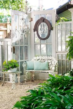 Hinged together, salvaged French doors add decorative oomph to the outdoor seating area outside this gorgeous garden house. Get the look: White iron bench ($112; amazon.com), French door ($149; homedepot.com), Looking glass silver-like spray paint ($9; amazon.com), Chandelier ($88; amazon.com)