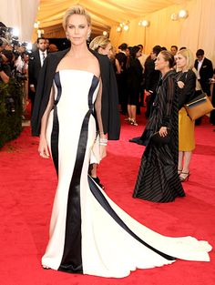 Charlize Theron is gorgeous in a white gown by Dior Haute Couture, a Dior black wool jacket and a Dior clutch at the 2014 Met Gala