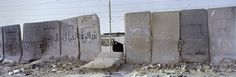 A wall running through Shiite Sadr City in Baghdad. The wall was erected by the U.S. Army to protect an area from attack of the Mehdi Army, a Shiite militia following Muqtada al-Sadr, a Shiite cleric in the rank of a Sayyid. The wall is still in place and heavily guarded by the Iraqi army but inhabitants hit a number of holes in it or removed slabs. Iraq, January 2012. Photo: From Confrontier by Kai Wiedenhöfer published by Steidl.   eklectica.in