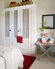 Bedroom red & white: built-in closet, just not recessed. It looks like a big, beautiful built-in armoire. A great example of how to add a little closet space in an office or bonus room to turn it into a guest bedroom.