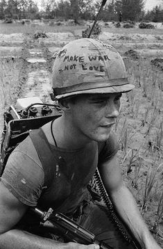 """21 Sep 1967, Da Nang, South Vietnam --- Da Nang, South Vietnam: Marine Cpl. Michael Wynn, 20, of Columbus, Ohio, seems to be trying to get a message across with a takeoff of the hippie slogan """"make war not love"""" written on his helmet here. Wynn is taking a breather during Operation Ballistic Charge. 9/21/67 --- Image by © Bettmann/CORBIS"""