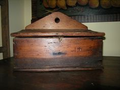 "This circa 1790-1820 early hanging salt box is magnificent. This was used for 'salt crystals' and it shows the corrosive effect of raw salt on unprotected wood. The bottom of the box is darkened due to salt damage over many, many years. It was found in Virginia and like other pieces of this age, it was never painted but has the most wonderful patina to the wood. Made of southern pine.  It is 11 x 5 x 6"" deep not including the triangular back and 8"" tall if you include the back. $ 338.00"