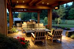 This covered country patio features cushioned outdoor furniture, a fire pit, dining area and an outdoor kitchen for effortlessly hosting and entertaining guests.
