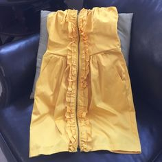Bright Yellow Dress Strapless mini dress. Ruffle all the way down middle held together by a zipper. Two angled pockets on sides. Stretch & Satiny feel. Hanger straps have been cut off. Wishes Wishes Wishes Dresses Strapless