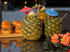 Kalua pork sliders and fancy drinks in pineapples.