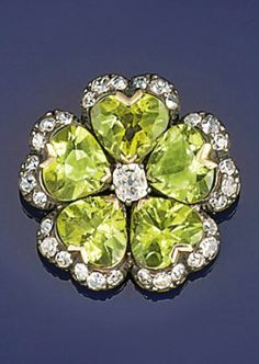 A peridot and diamond brooch  Of flowerhead design, the central cushion shaped diamond to heart shaped peridot petals and diamond border, circa 1900