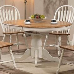 ECI furniture  Crafted from softly finished solid oak accented with antique white trim, this round single pedestal dining table features a turned column base and feet with levelers. A convenient self-storing butterfly leaf is included to expand the table