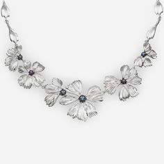 A silver statement necklace with six flower-shaped segments crafted in 925 sterling silver with black freshwater pearls set in the center of each segment. https://zanfeldjewellery.com/wholesale/necklaces/silver-statement-necklace-black-pearls/
