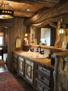 Cast iron sink, wood slab countertop, and birch bark covered doors and drawer fronts give this vanity a delightfully rustic feel. - #WesternHome