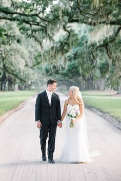 Bride and groom walking up the iconic tree lined driveway at their BOONE HALL PLANTATION wedding // by Charleston wedding photographers Aaron and Jillian Photography