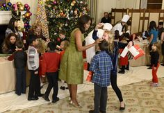 First Lady Michelle Obama (C) chats with children of military families as they gather to enjoy holiday decorations and treats at the White House, in Washington, December 2, 2015.