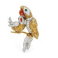 >Cartier, circa 1962. Clip de corsage en or jaune et platine ciselé d'un perroquet et de son petit sur une branche, sertis de diamants jonquille et blancs, les yeux sertis d'émeraudes, les becs en corail.