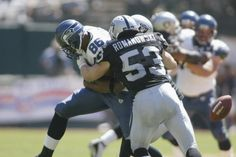 Tight End Jerramy Stevens of the Seattle Seahawks loses the football while being hit by linebacker Bill Romanowski of the Oakland Raiders during the...
