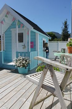 inside a DIY painted play shed for girls. Do you need some childrens shed ideas? Make your own little playhouse for your kids & paint it in bold, bright colors. This little painted play shed/kids hut is adorable and would look fabulous in your garden!
