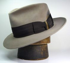 """The GOLDFINCH Shown in pecan 100% beaver felt. The Goldfinch wears a 2"""" triple pressed espresso ribbon. The bow is trimmed with a brass wrap and a few feathers just for good measure. Crown 4 1/2"""" in front, 3 3/4"""" in back 2 1/2"""" brim with underwelt"""