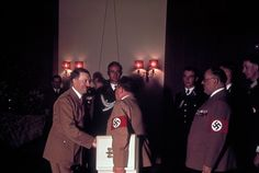 Adolf Hitler's 50th Birthday, 1939 Germany. Hitler shakes hands with one of his personal photographers, Heinrich Hoffmann, while his doctor, Theodor Morrell (right) waits to greet the Fuhrer on Hitler's 50th birthday, April 20, 1939, in Berlin.