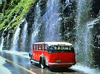 Jammer bus going by the Weeping wall in Glacier National Park, Montana