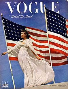 """Like the Statue of Liberty came to life & decided to wear white! The TWO flags create DRAMA, too. Dress not my favorite. """"United We Stand"""" intensifies message. Pub date?"""