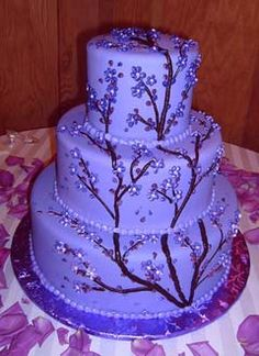 """Lavendar and deep purple cherry blossom round fondant wedding cake with Chocolate brown accents. Decorated with dark chocolate """"tree limbs and branches"""", with purple and lilac flowers and buds.From www.glassslippergourmet.com         ........   #wedding #cake #birthday"""