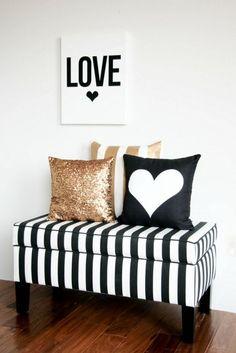 Decoração com preto, branco e dourado.Puff listrado , almofadas fofas e quadro.