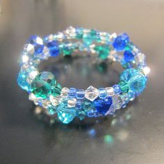 Blue water memory bracelet.     Three rows of memory wire strung with sparkling blue and green bicones and rondels and silver and green Swarovski beads. Fun bracelet! Will retain its shape. If you need it smaller or larger, just mold the bracelet to your size wrist. http://newlyfoundtreasures.etsy.com    Matching earrings at http://www.etsy.com/listing/90880438/blue-water-earrings?ref=v1_other_1