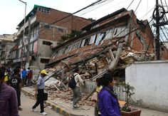 Nepalese people walk past a collapsed building in Kathmandu after an earthquake on April 25, 2015.