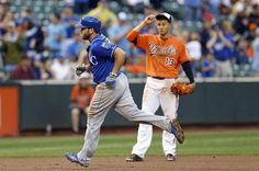 Kansas City Royals' Mike Moustakas, left, rounds the bases past Baltimore Orioles third baseman Manny Machado after hitting a grand slam in the seventh inning of a baseball game, Saturday, Sept. 12, 2015, in Baltimore.