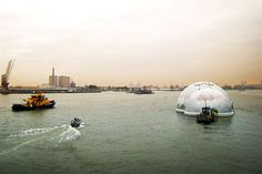 The Floating Pavilion Rotterdam, seen here on the Netherlands' Nieuwe Maas River, was designed by DeltaSync and Public Domain Architecten. Made from steel beams and covered with lightweight, translucent ETFE film, the structure serves as a portable exhibition hall and conference space.