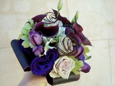 Sweet Floral's bridal bouquet of purple Calla lilies, green dendrobium orchid, purple lissianthus and peacock feathers.