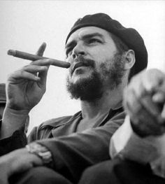 Revolutionary Che Guevara - on viewing stand smoking big cigar at an anniversary celebration of the Cuban revolution.