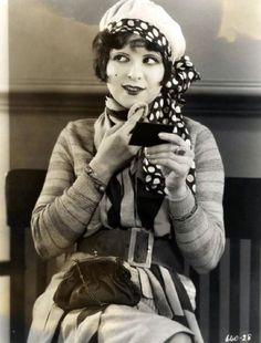 Clara Bow with compact ~ Beauty is the fashion in 1925. The Flapper is frankly, heavily made up, not to imitate nature, but for an altogether artificial effect—pallor mortis, poisonously scarlet lips, richly ringed eyes—the latter looking not so much debauched (which is the intention) as diabetic. Her walk duplicates the swagger supposed by innocent America to go with the female half of a Paris Apache dance.