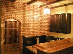 Basement wet bar and wine cellar with brick walls, stone floors and wood beam ceilings.