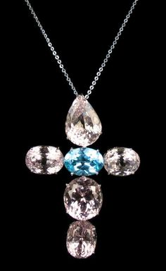 Blue Topaz, Kunzite, and Diamond Cross Pendant Necklace. Accompanied by 7.16 carats of Blue Topaz, 55.50 carats of Kunzite, and 0.45 carats of Diamonds (diamonds set in an 18 karat White Gold chain). Fully set in 18 karat White Gold.