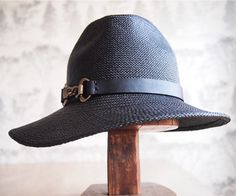 Eloise: Assymetrical side swept brim with fedora style crown in black panama straw with black leather trim and chain
