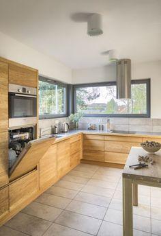 W kuchni duże panoramiczne okna pozwalają pracującym tu domownikom cieszyć się otaczającą zielenią. Zmywarka została zabudowana około 40 cm ponad posadzką, dzięki czemu załadunek i rozładunek jest wygodniejszy niż przy standardowym rozwiązaniu tuż przy ziemi