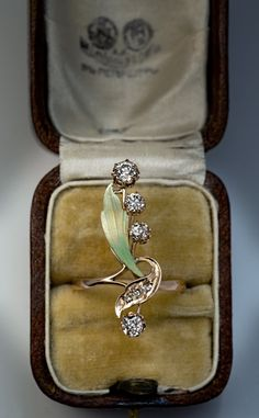 made in Moscow between 1908 and 1917 A 14K gold ring is designed as a stylized flower embellished with painted pale golden green enamel and champagne color
