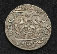 World coins - India Silver Rupee issued by Ghazi-und-Din Haidar, King of Awadh, Mint Year 1820.  Obverse: Crown above Katar dagger, flanked by rampart lions holding flag. Two upright fish flanking regnal year (7) below. Legends around.