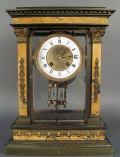 """A Louis XVI style bronze and Seina marble overmantle clock with a damascened and enamel face and its original mercury pendulum. CIRCA: 1880 DIMENSIONS: 12.6"""" h x 9.4"""" w x 5.5"""" d"""